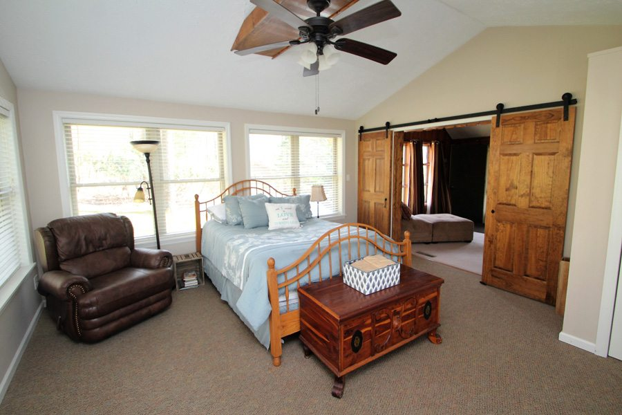 The addition bedroom is separated from the living room by sliding barn doors.