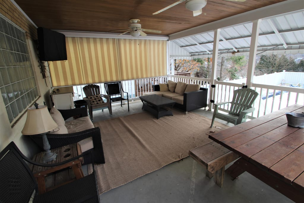 View of Back Covered Porch with loads of seating overlooks the pool!