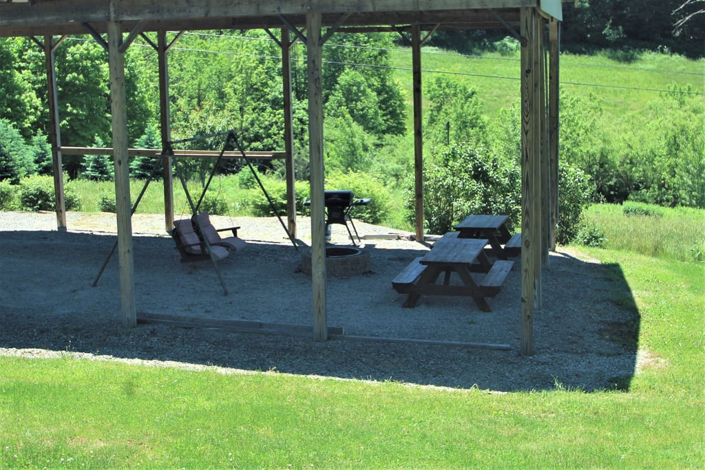 Shaded Pavilion with picnic tables and fire pit are common/shared by all guests.