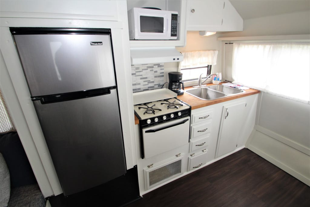 Efficient kitchen with stove top, microwave and refrigerator