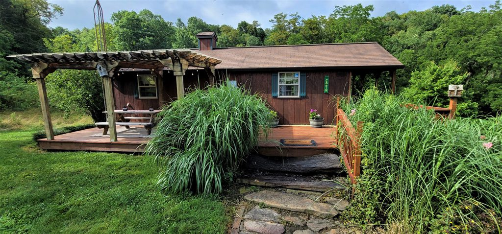 Enjoy the pergola, picnic table and full length deck along the cabin!
