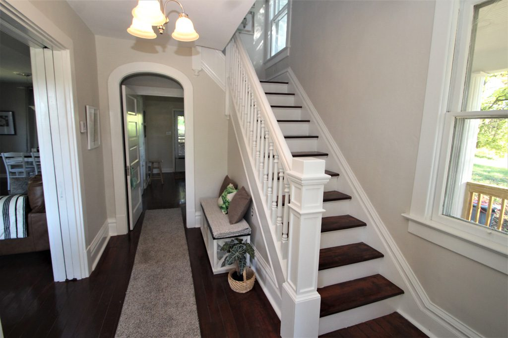 As you step into the farmhouse, you'll see an arched doorway & stairs to 2nd fl.